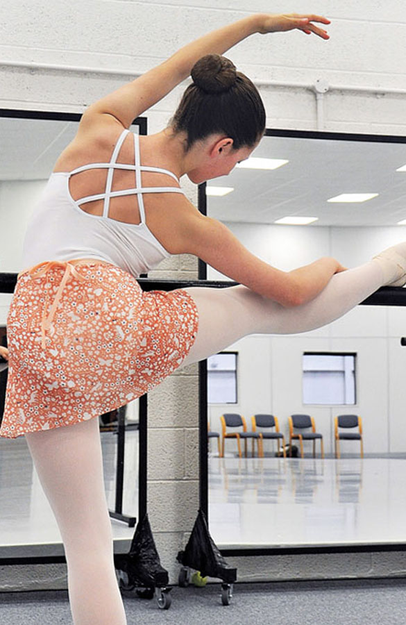 A ballerina stretching in a barre in a pink Chiffon skirt with ditsy flora print.