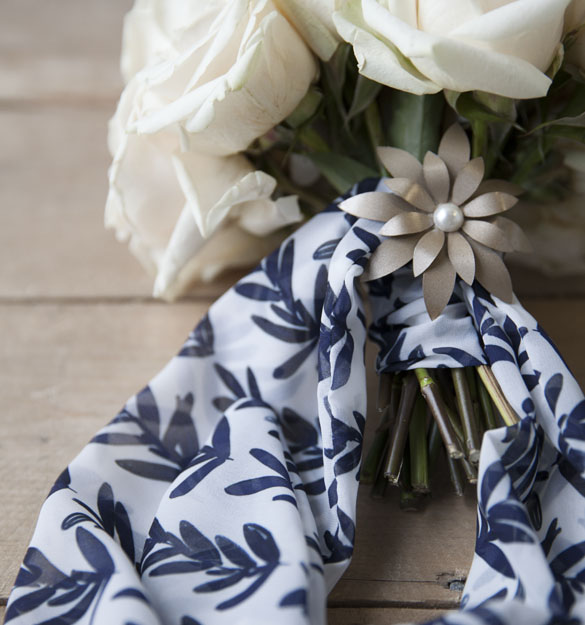 Bouquet of white roses wrapped with white Chiffon fabric with a navy sage pattern.