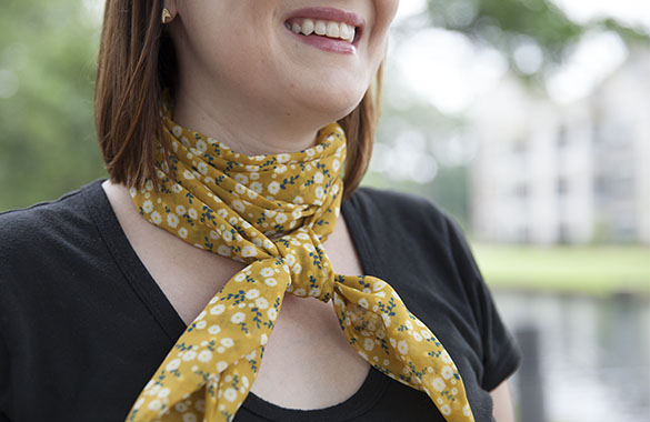 Headshot of a smiling woman in a black shirt wearing a yellow Chiffon scarf with daisy print.