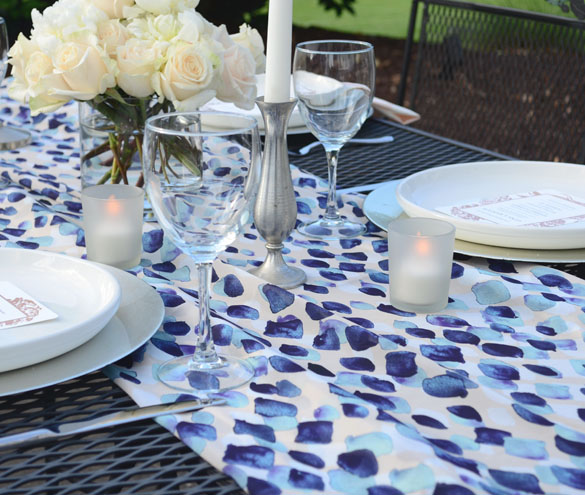 Outdoor tablescape setting with white dinner plates, candles, flowers and blue abstract raindrop print Chiffon tablerunner.