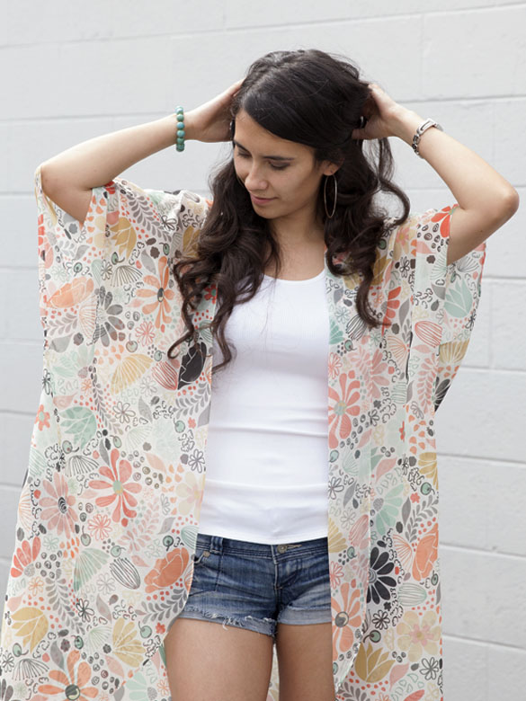 Woman in white tank top, denim jeans and pastel wildflower printed Chiffon kimono.
