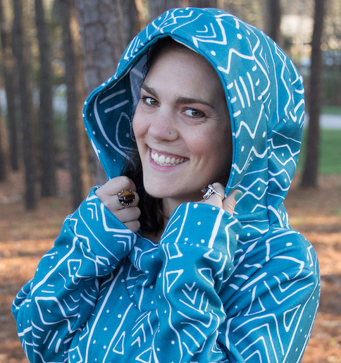 Headshot of woman wearing a teal and white African mudcloth pattern hoodie with hood pulled up.