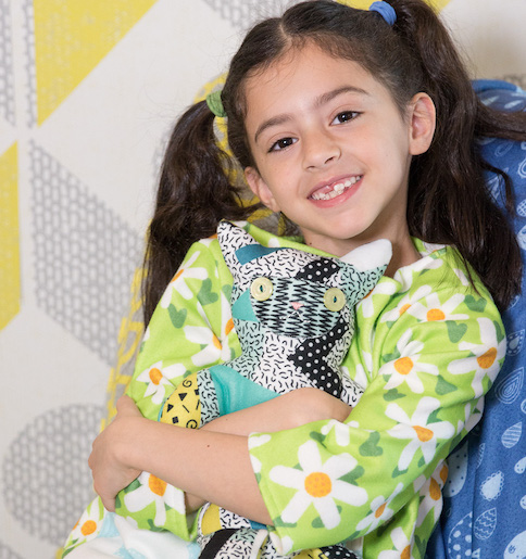 Young smiling girl holding a fleece monster plushie and wearing green fleece shirt with white daisies.