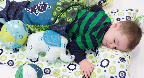 Toddler napping on fleece green and blue gears nap map with fleece blanket.