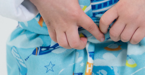 Small child's hands holding blue fleece blanket with multi colored rocket ships.