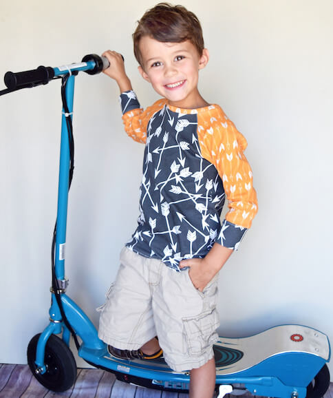 Child standing on a scooter