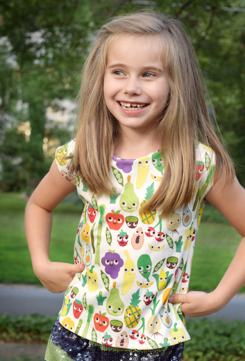 Girl standing outside wearing a t-shirt with colorful fruit and vegetable designs