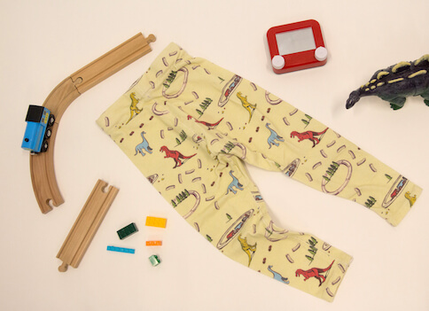 A pair of baby leggings arranged on the floor with toy dinosaur and trains