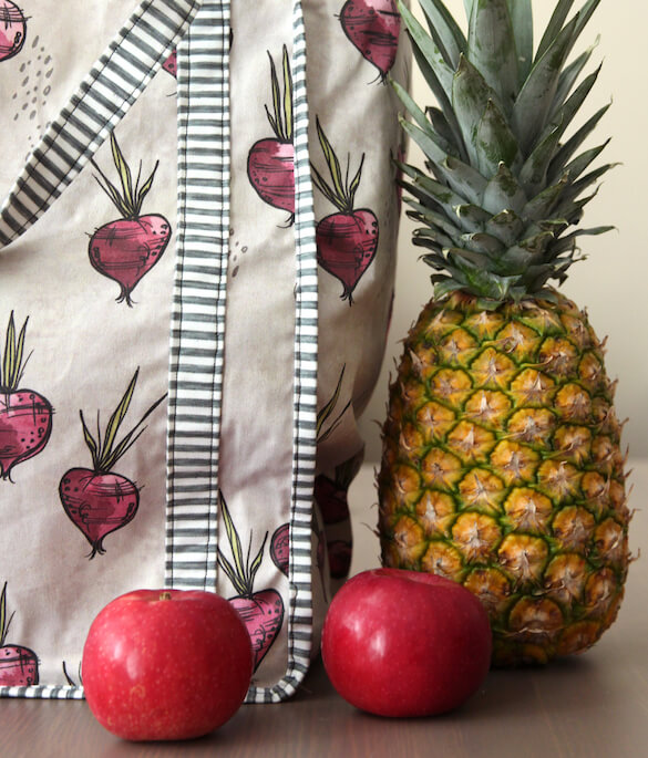Apples and pineapple next to a Lightweight Cotton Twill tote bag featuring a vegetable design