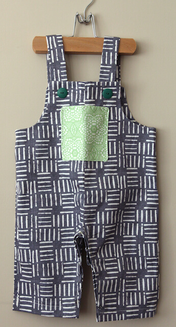 An adorable pair of toddler overalls made in a gray and white wicket design with a green and white dot patterend front pocket.