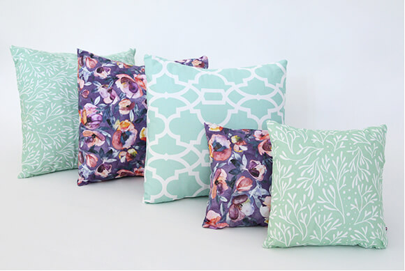5 heavy cotton twill accent pillows featuring green and white leaf patterns and purple and peach watercolor patterns.