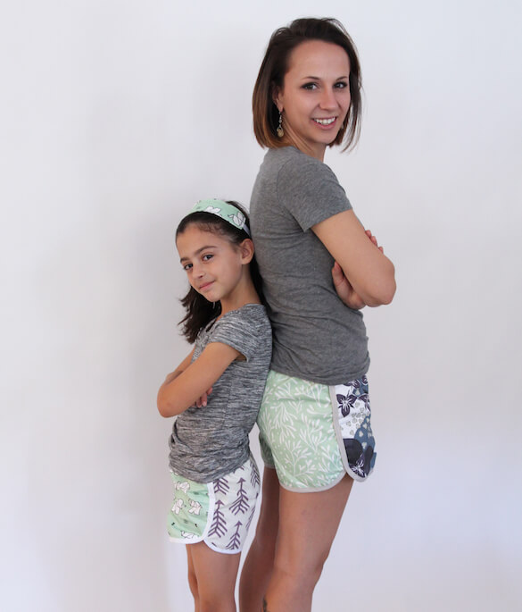A mother and daughter, back to back wearing lightweight cotton twill fabric shorts. Patterns include green and white elephants, purple arrows and puple and blue plums.