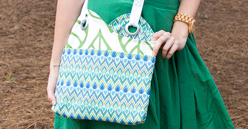 Woman in green dress modeling a green, blue and white Linen Cotton Canvas Ultra sidekick bag.