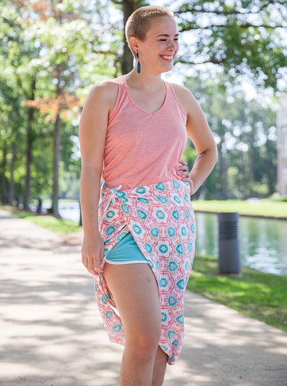 Smiling woman standing outisde modelng a pink and teal floral Organic Sweet Pea Gauze sarong over swim short.