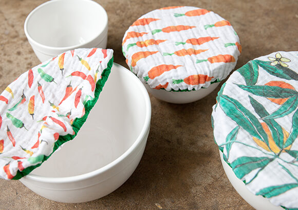 Ceramic mixing bowls on counter top with Organic Sweet Pea Gauze cloth bowl covers on top with vegetable prints.
