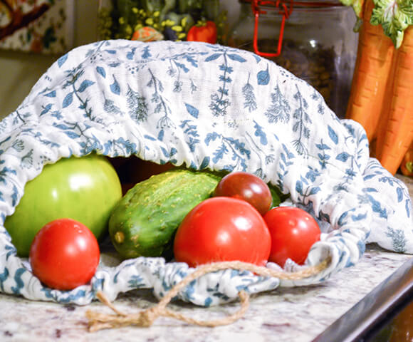 Fresh summer produce spilling out of an Organic Sweet Pea Gauze white and sage colored herb print on counter top.