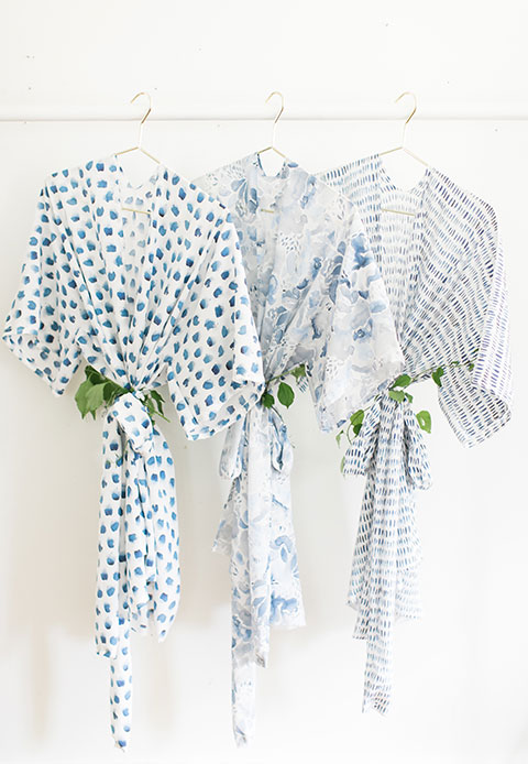 3 translucent blue and white floral watercolor print poly crepe de chine kimonos in a row on hangers.