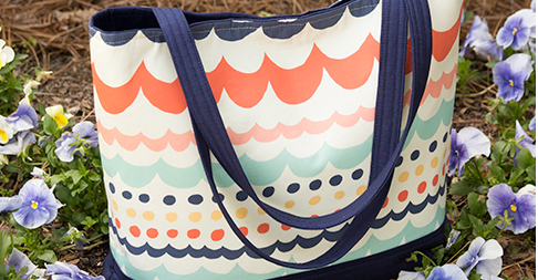 Tote bag with multi-color scalloped and polka dog design with blue trim and handles in flower bed.
