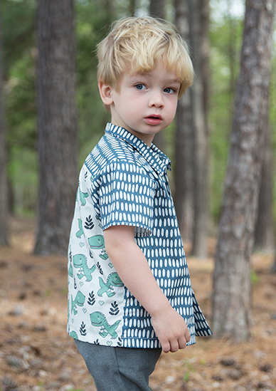 Boy in collard cotton poplin shirt with dinosaur and confetti style blue dot pattern.