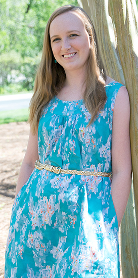 Young woman in sleeveless turquoise cotton poplin dress with floral design.