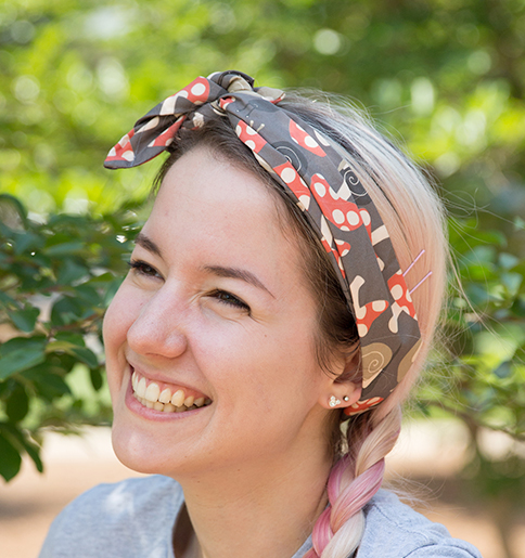 A smiling young woman with a red and white mushroom print on gray Organic Cotton Sateen Ultra headband.