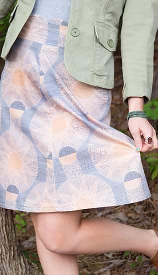 A woven textured sun design in orange featured on a gray Organic Cotton Sateen Ultra fabric.